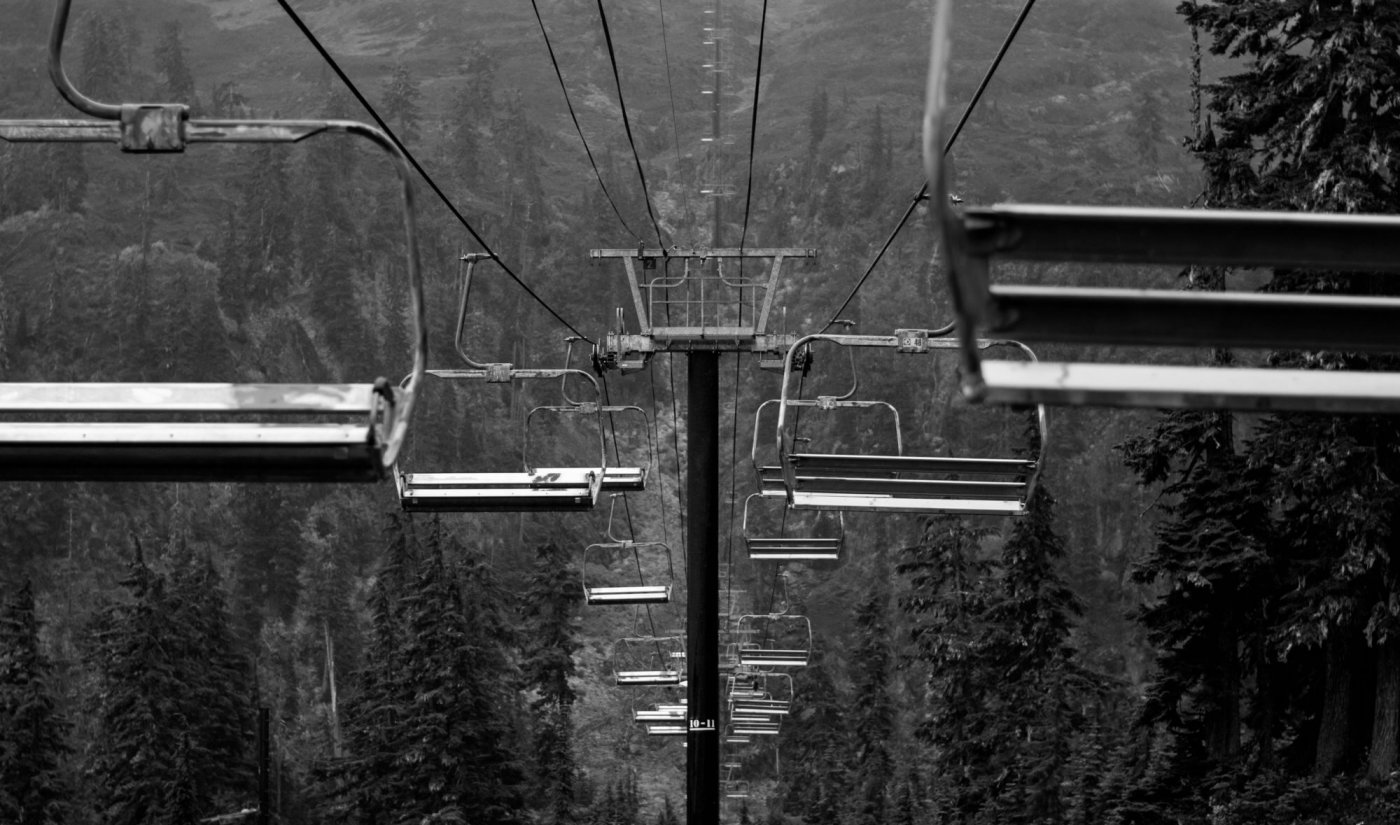 Chair lift on the top of a mountain covered in trees during the offseason of a ski resort